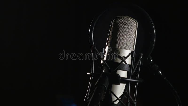 Microphone sur un support situé dans une cabine d'enregistrement de studio de musique sous la lumière discrète images stock