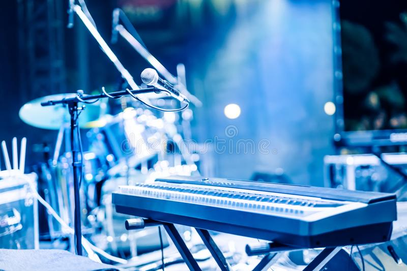Microphone and synthesizer on stage. Microphone and synthesizer on concert stage with defused bokeh lights blue colour background stock photo