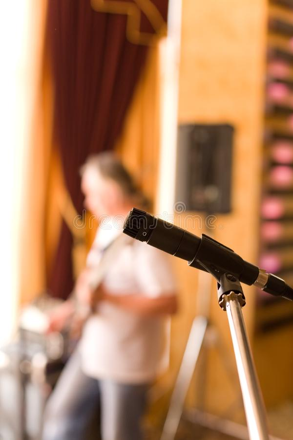 Microphone on tripod with guitarist on background stock photo