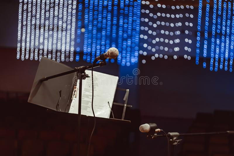 Microphones in the concert hall. Microphone on the stand in the concert hall, burning lights on the background royalty free stock photo