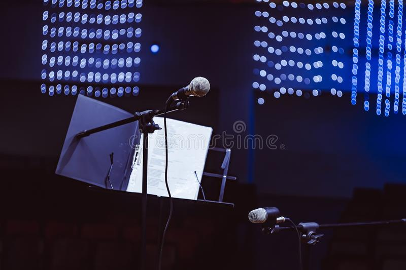 Microphones in the concert hall. Microphone on the stand in the concert hall, burning lights on the background stock photo