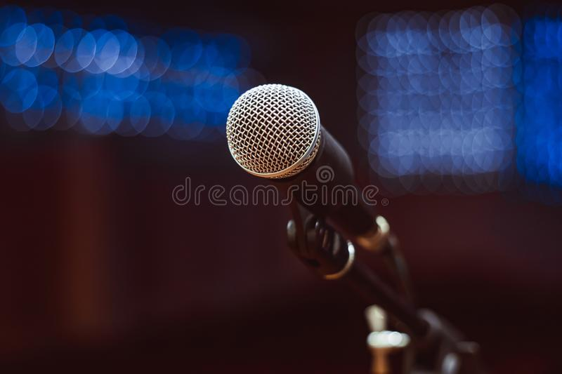 Microphones in the concert hall. Microphone on the stand in the concert hall, burning lights on the background royalty free stock image