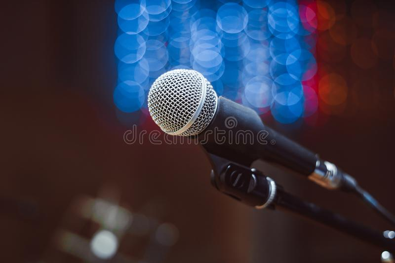 Microphones in the concert hall. Microphone on the stand in the concert hall, burning lights on the background stock image