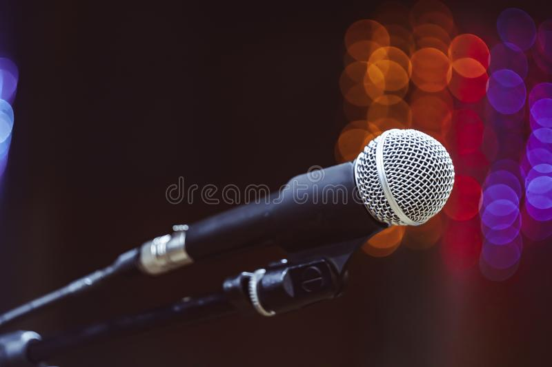 Microphones in the concert hall. Microphone on the stand in the concert hall, burning lights on the background stock images
