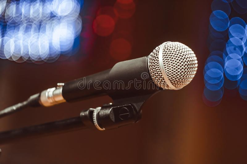 Microphones in the concert hall. Microphone on the stand in the concert hall, burning lights on the background royalty free stock photos