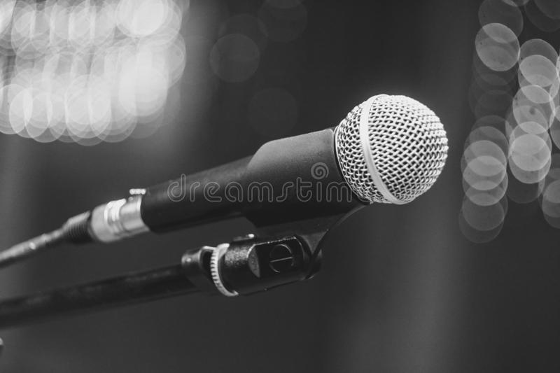 Microphones in the concert hall. Microphone on the stand in the concert hall, burning lights on the background stock photos