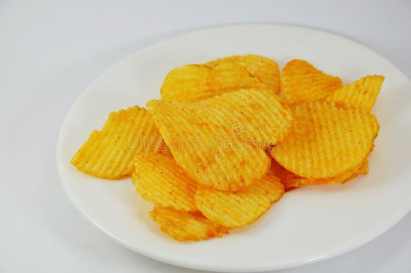 Microplaqueta de batata no prato fotografia de stock