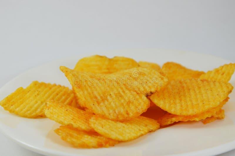 Microplaqueta de batata no prato foto de stock