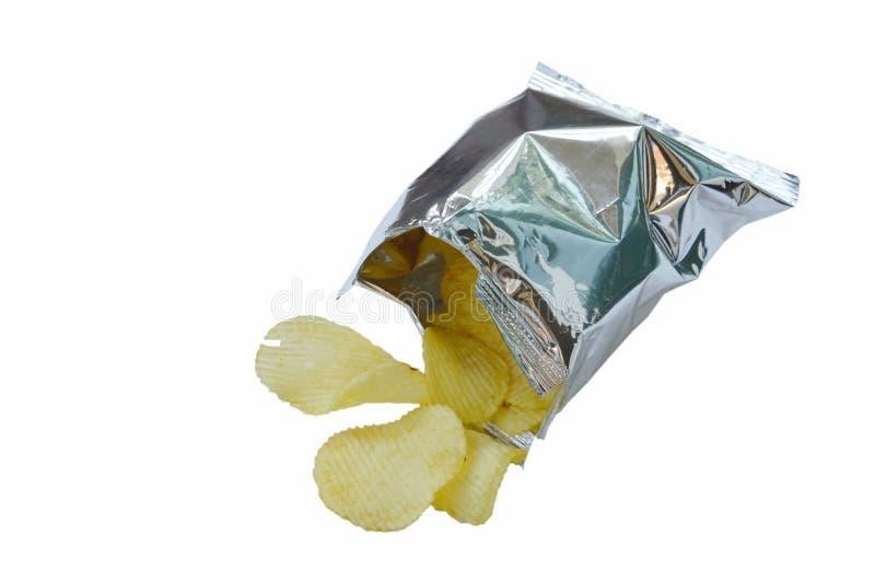 Microplaqueta de batata que derrama da folha de alumínio que empacota no fundo branco imagens de stock royalty free