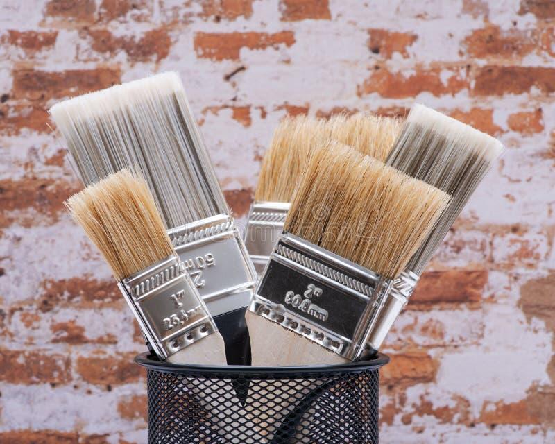 A microplaqueta e o plano lisos cortaram escovas de pintura de serviço público na parede de tijolo imagens de stock