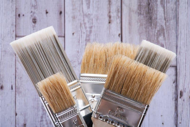 A microplaqueta e o plano lisos cortaram escovas de pintura de servi?o p?blico na madeira foto de stock