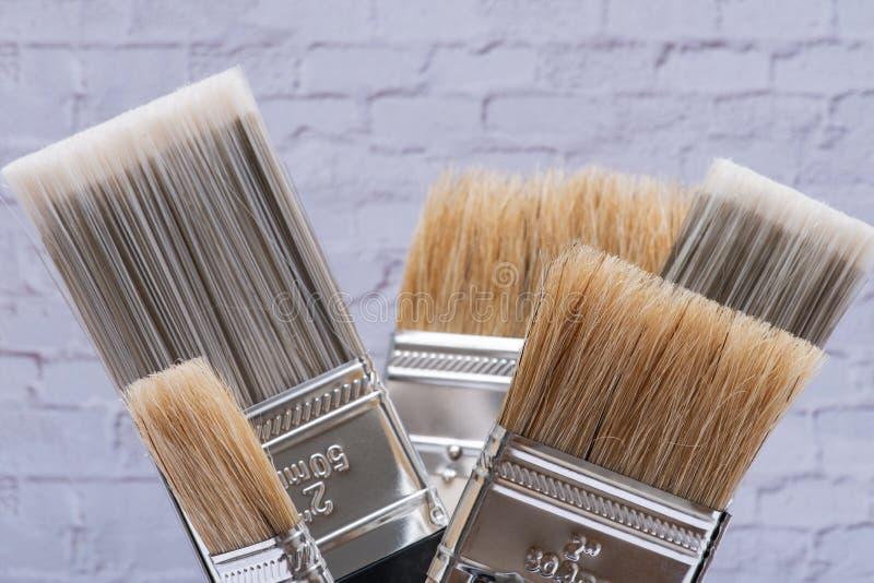 A microplaqueta e o plano lisos cortaram escovas de pintura de servi?o p?blico na parede de tijolo fotos de stock royalty free