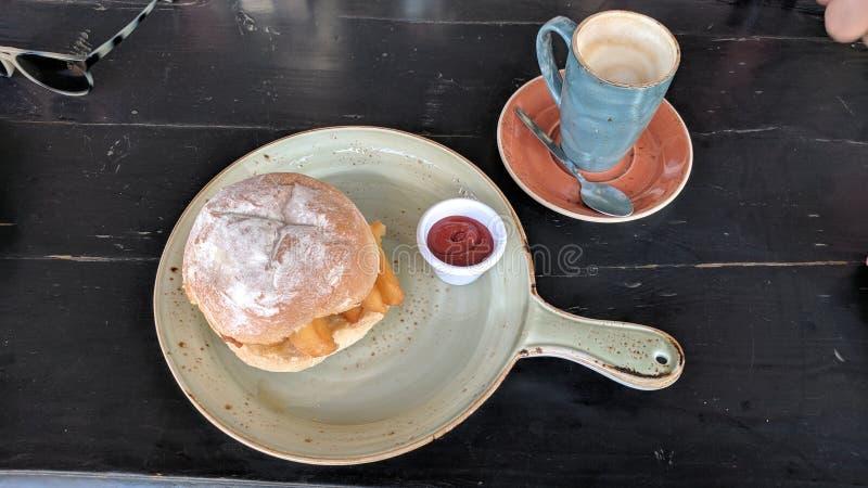 Microplaqueta gourmet butty com ketchup e um café fotos de stock