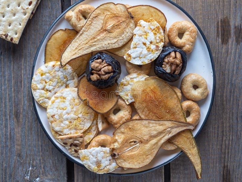 Microplaquetas úteis dos cereais e frutos e ameixas secas secados com porcas em uma placa cerâmica disparada do de perto em uma p fotografia de stock royalty free
