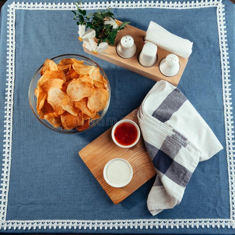 Microplaquetas de batata com molho na tabela Molhos caseiros foto de stock royalty free