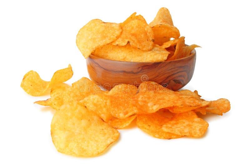 Microplaquetas de batata deliciosas em uma bacia de madeira isolada no fundo branco, incluindo o trajeto de grampeamento sem másc imagem de stock