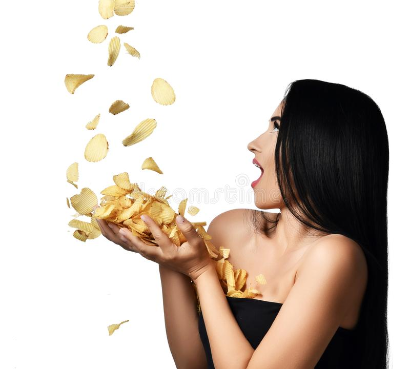 Microplaquetas de batata do Riffle que caem nas mãos da mulher isoladas em um branco Surpreendeu o sorriso feliz Conceito insalub imagem de stock