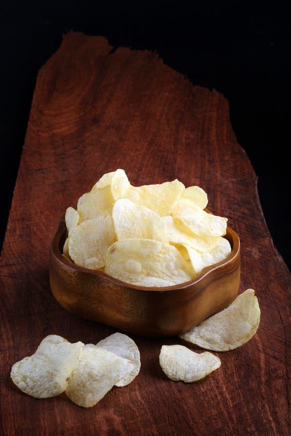 Microplaquetas de batata friáveis na bacia de madeira na bandeja e na parte traseira de madeira do preto fotos de stock royalty free