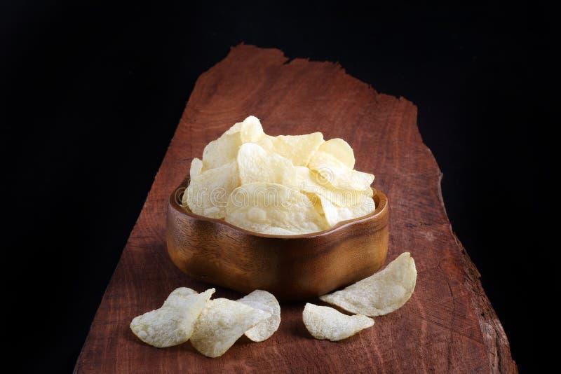 Microplaquetas de batata friáveis na bacia de madeira na bandeja e na parte traseira de madeira do preto fotografia de stock