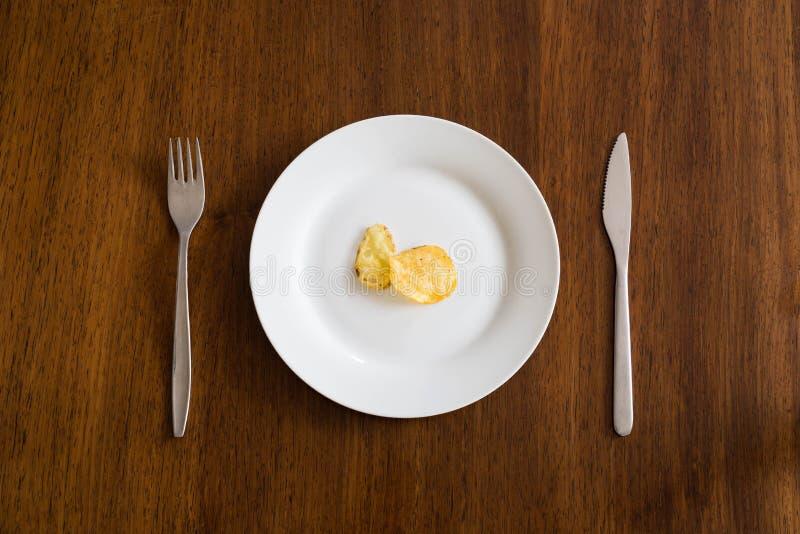 Microplaquetas de batata na placa branca na tabela de madeira com faca e forquilha fotografia de stock royalty free