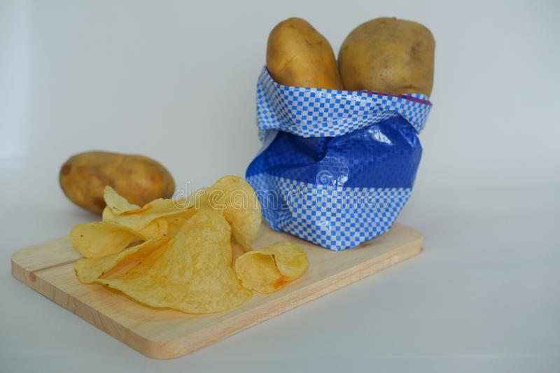 Microplaquetas de batata na placa de corte e no fundo branco imagens de stock royalty free