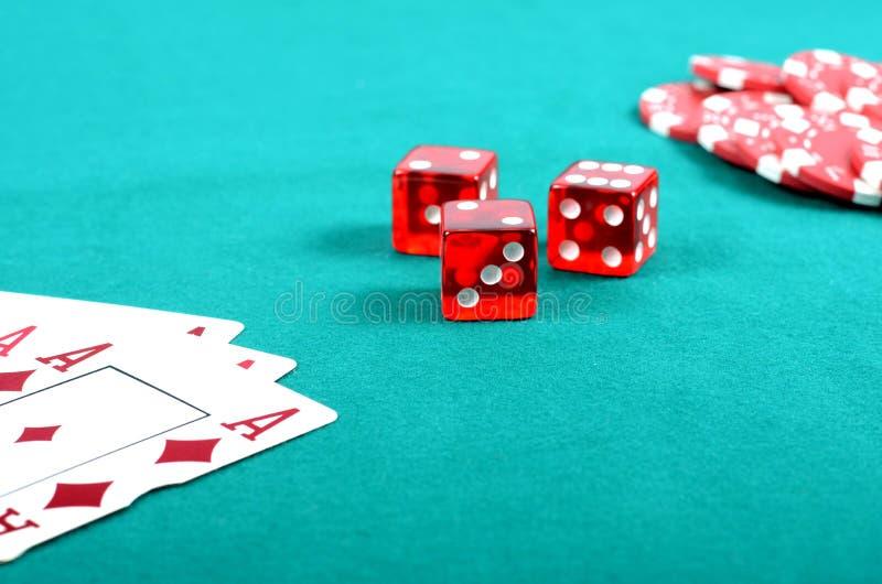 Microplaquetas de jogo do póquer vermelho em uma tabela de jogo verde fotos de stock royalty free