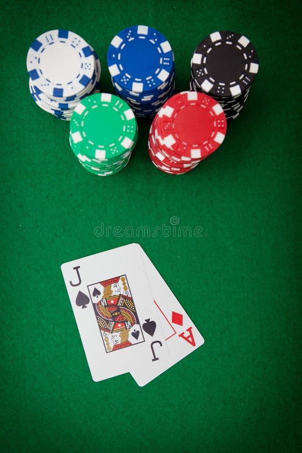 Microplaquetas de jogo no feltro do casino e na mão de vencimento dentro foto de stock royalty free