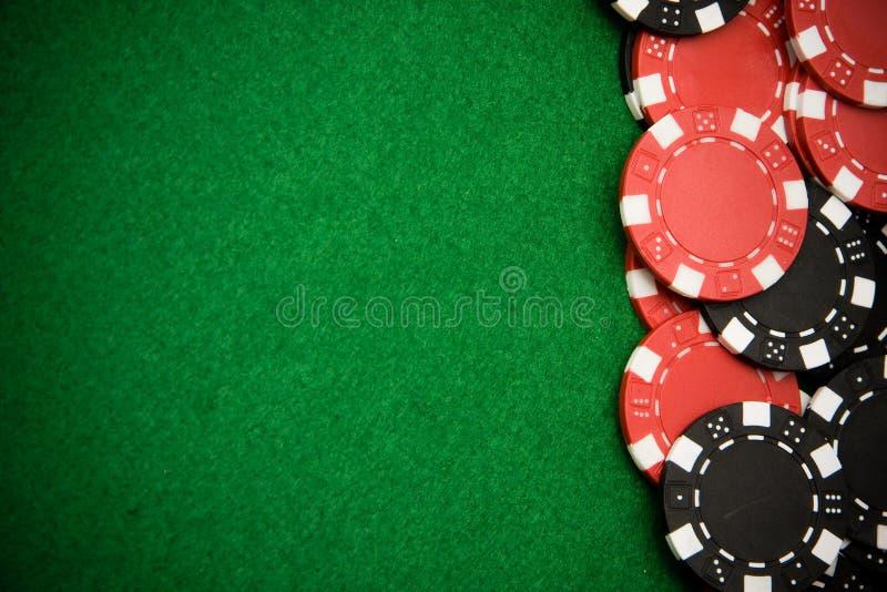 Microplaquetas de jogo pretas e vermelhas no fundo verde imagem de stock royalty free