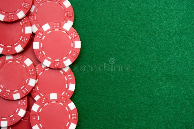 Microplaquetas de jogo vermelhas no fundo verde fotos de stock