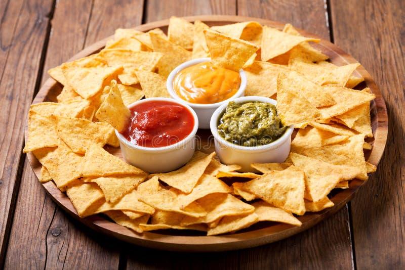 Microplaquetas de milho mexicanas dos nachos com mergulho do guacamole, da salsa e de queijo imagem de stock royalty free