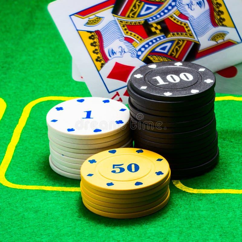 Microplaquetas de pôquer redondas brilhantes e coloridas atrás que cai um rei do diamante do cartão de jogo imagem de stock royalty free