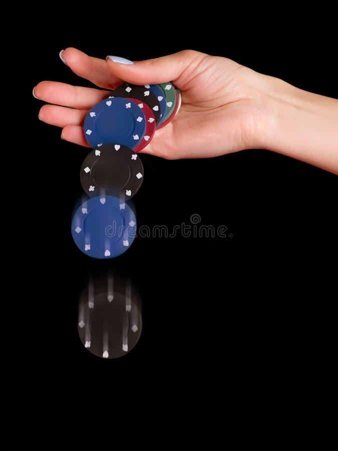 Microplaquetas de pôquer deixando cair da mão da mulher imagens de stock