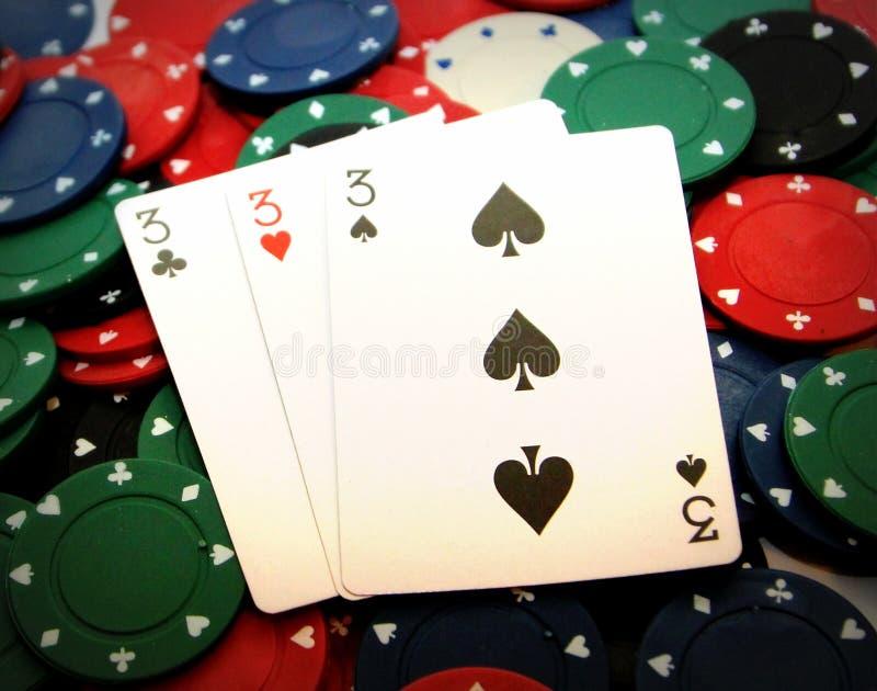 Microplaquetas de pôquer e trhees afortunados imagem de stock