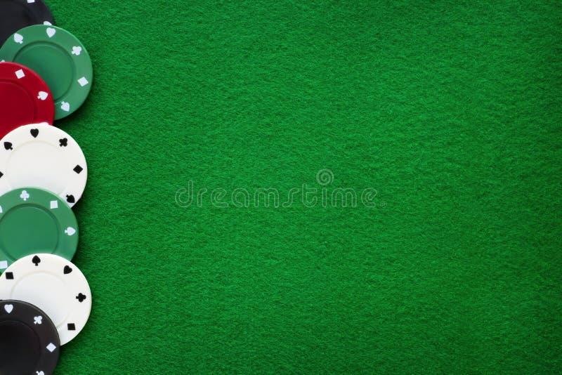 Microplaquetas de pôquer na tabela do casino de feltro do verde Jogo, pôquer, blackja fotografia de stock royalty free