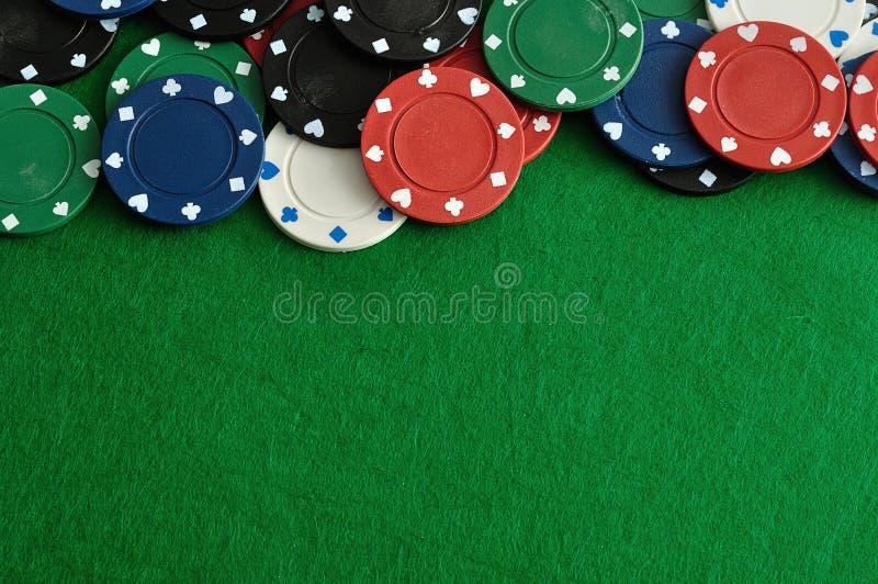 Microplaquetas de pôquer que formam um borde com um fundo verde imagens de stock