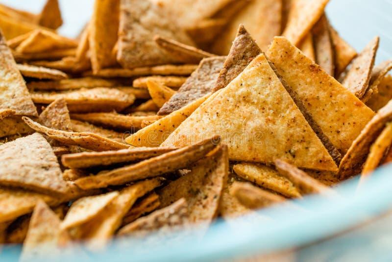 Microplaquetas de tortilha caseiros feitas com Flatbread e cozidas no forno/fim acima da vista macro imagem de stock