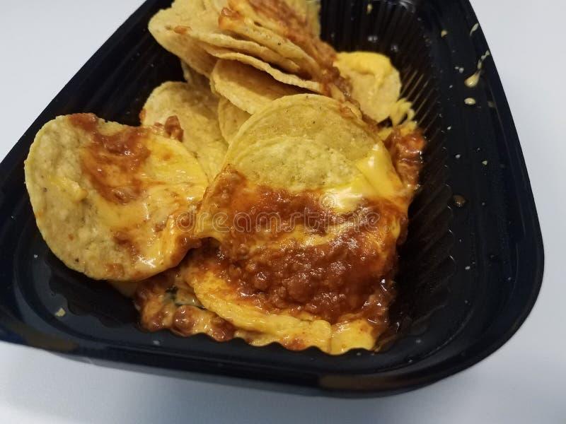 Microplaquetas de tortilha com molho do queijo e da carne no recipiente plástico preto imagens de stock royalty free
