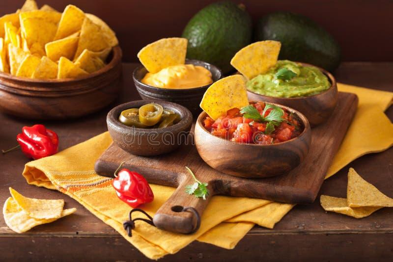 Microplaquetas de tortilha mexicanas dos nachos com guacamole, salsa e queijo d foto de stock royalty free
