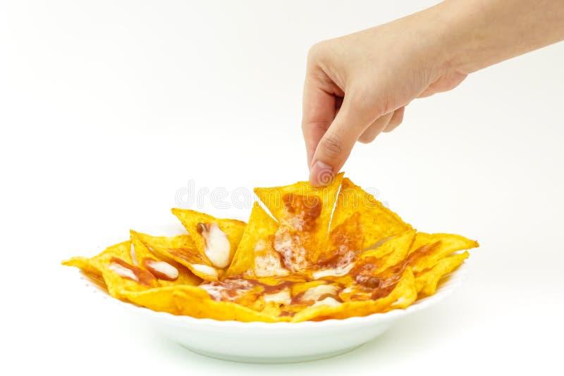 Microplaquetas do tortila de Pincking cobertas com o queijo (Nachos) de d branco fotografia de stock