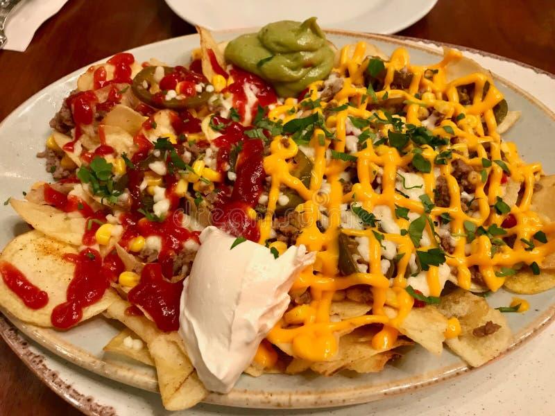 Microplaquetas dos Nachos com variedade derretida do queijo cheddar e dos mergulhos imagem de stock royalty free