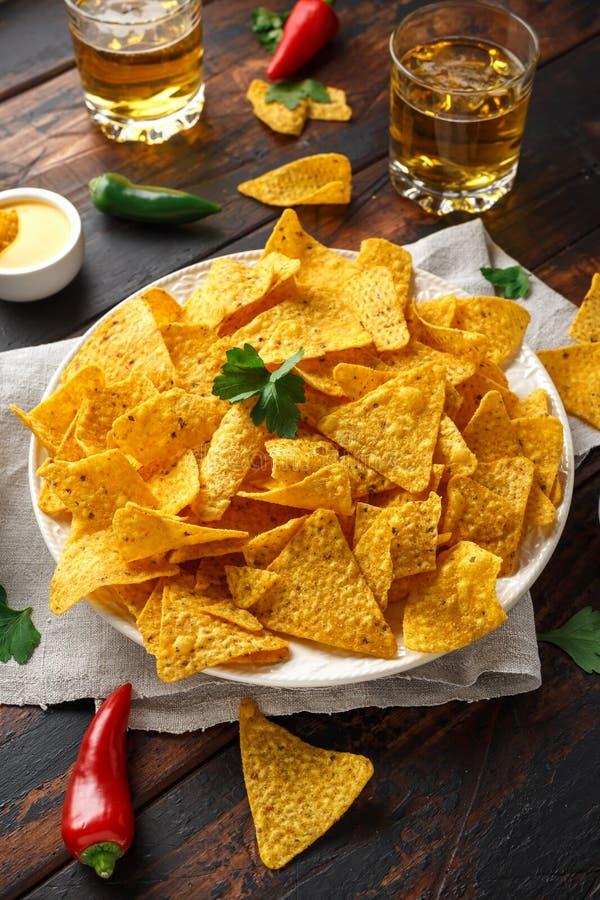 Microplaquetas dos nachos da tortilha com mergulho do molho de queijo, do guacamole e da salsa dos tomates Vidro da cerveja fotografia de stock royalty free
