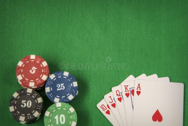 Microplaquetas e cartão de jogo para o pôquer no fundo de feltro do verde imagem de stock