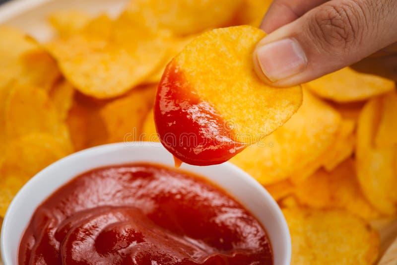 Microplaquetas e ketchup de batata petisco da cerveja, comer insalubre fotografia de stock royalty free