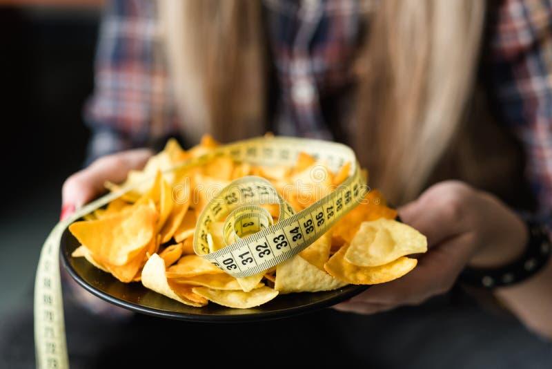 Microplaquetas más dos hábitos da nutrição do peso do petisco do fast food foto de stock