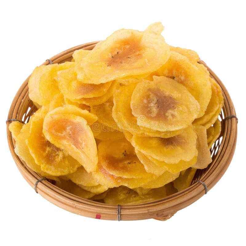 Microprocesadores secados del plátano en cuenco de madera Amarillee las rebanadas fritas de plátanos aislados en el fondo blanco fotografía de archivo libre de regalías