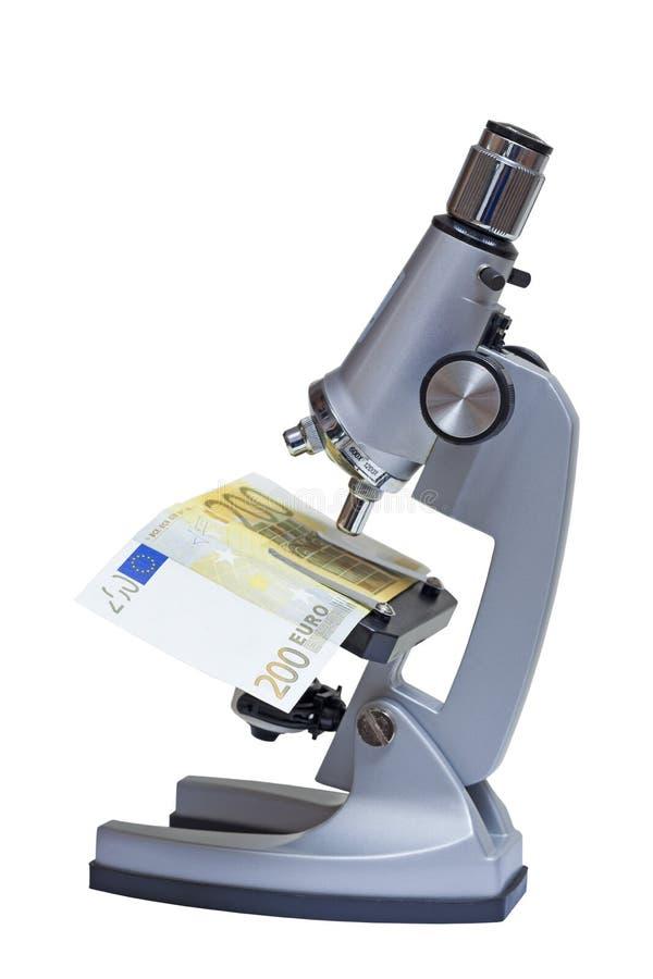 Microscópio com a euro- cédula no branco fotos de stock