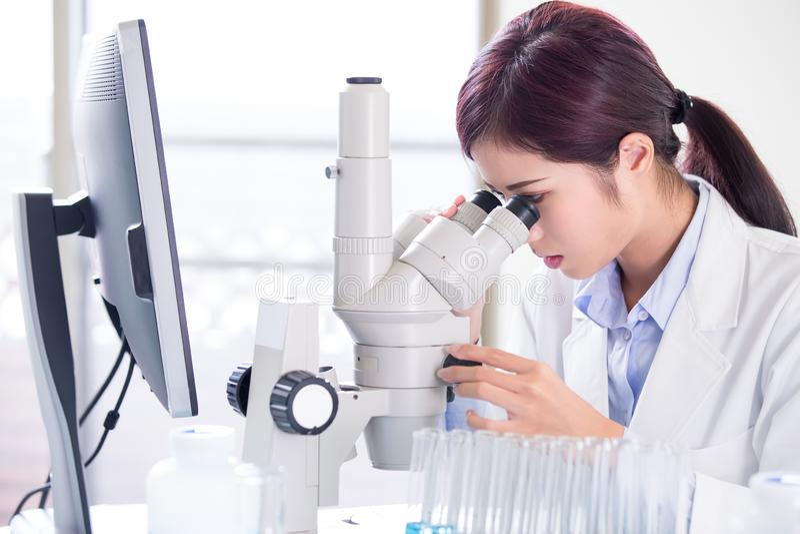 Microscópio do uso do cientista da mulher fotos de stock royalty free