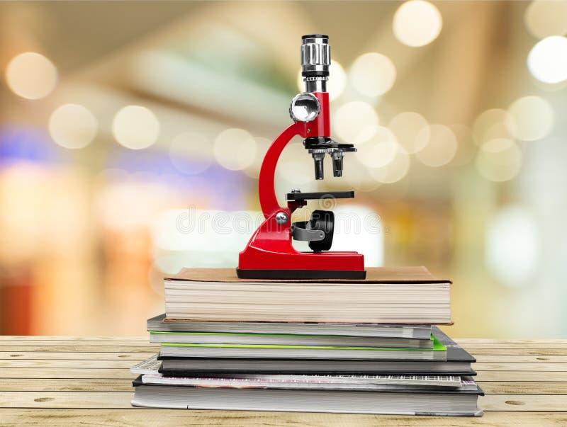 Microscópio e livros médicos na tabela de madeira fotos de stock royalty free