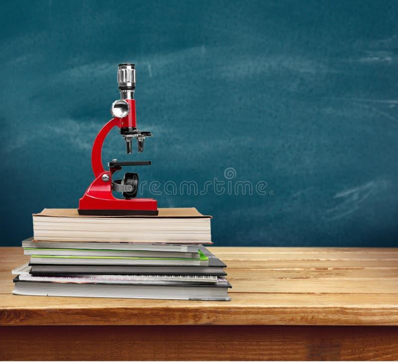 Microscópio e livros médicos na tabela de madeira imagem de stock royalty free