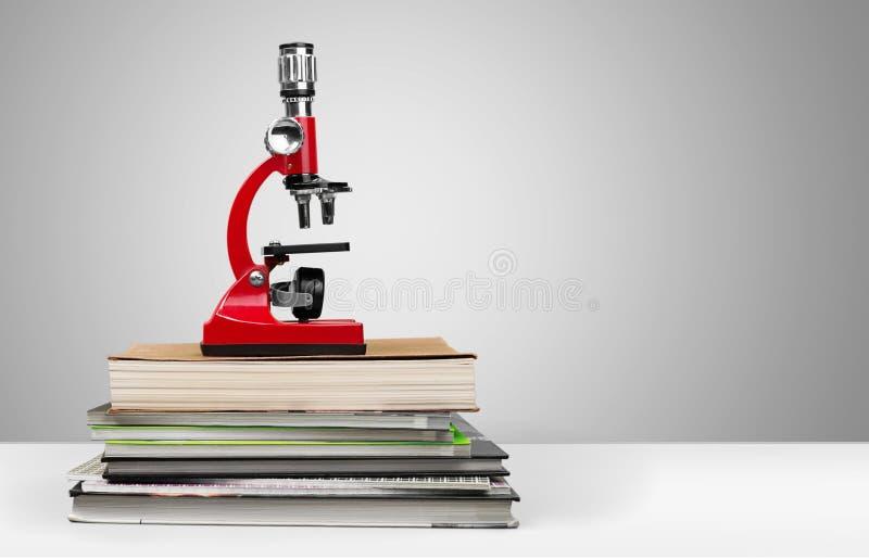Microscópio e livros médicos no fundo claro fotografia de stock